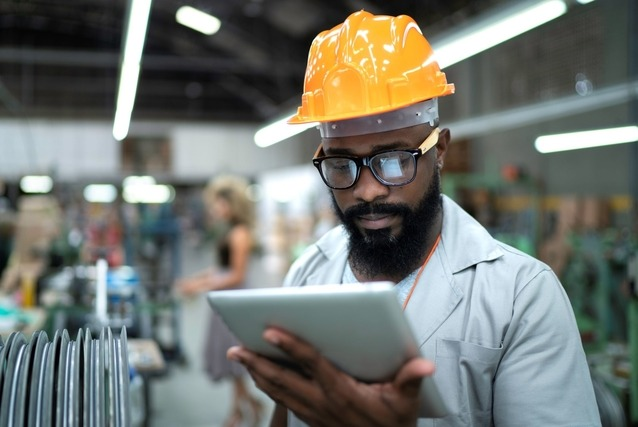 man holding tablet in manufacturing facility
